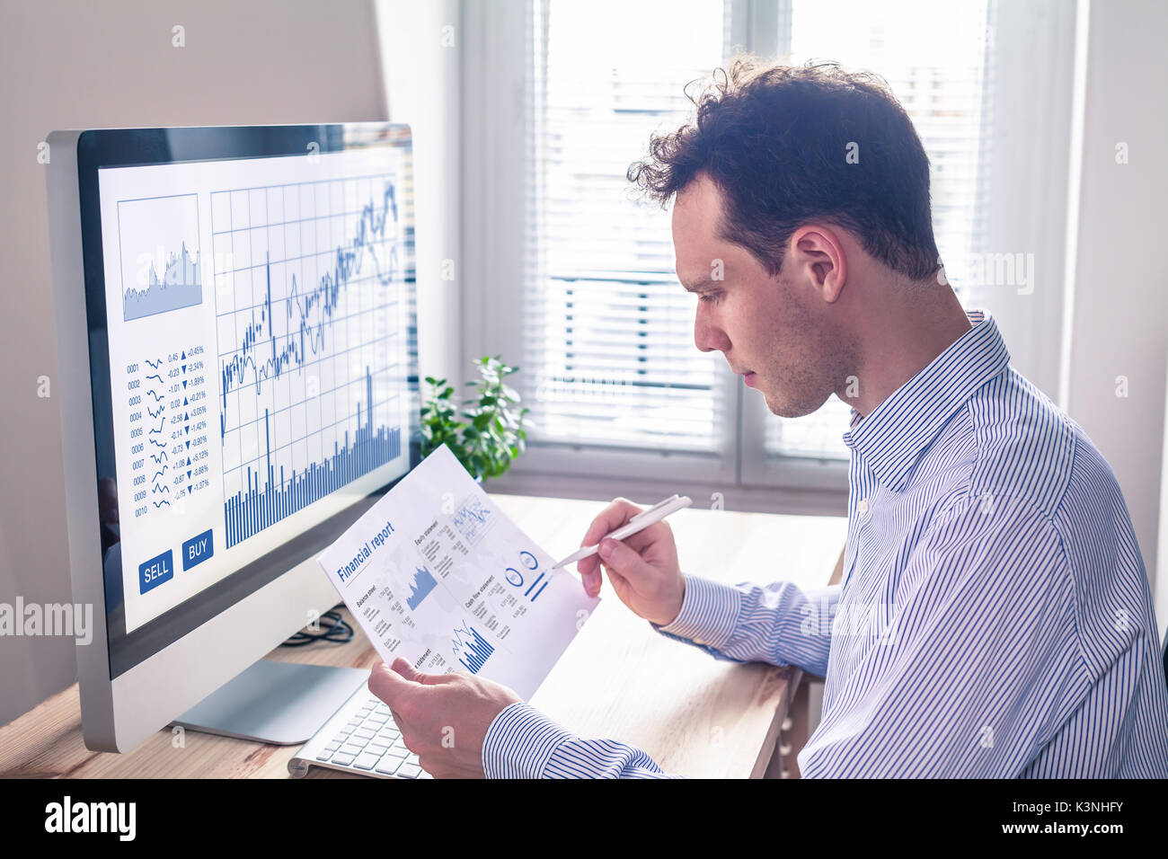 Trader analyzing financial report and trading charts and computer screen for successful sell buy strategy of stock market investment, fintech concept - Stock Image