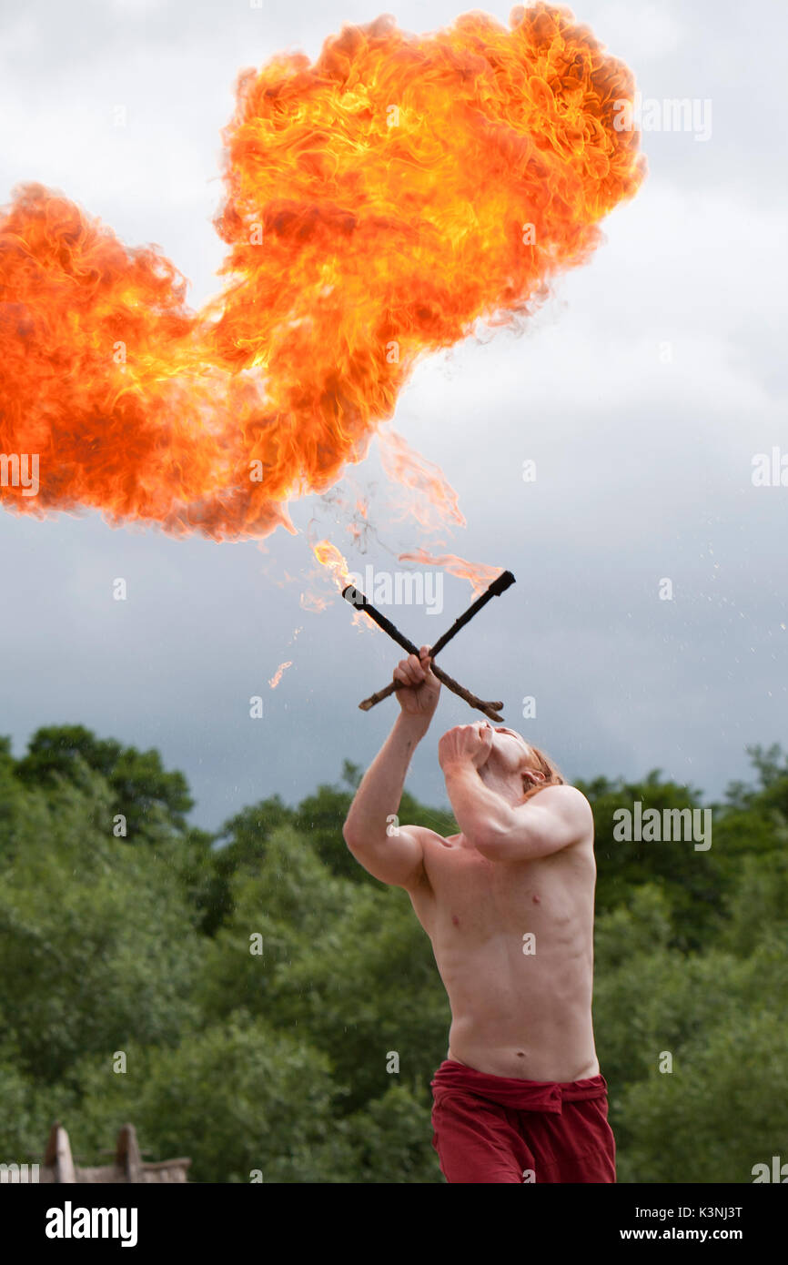Fire breather, Farren, blows a firey heart shape in the air during his fire act at Dragon Fest 2017. - Stock Image