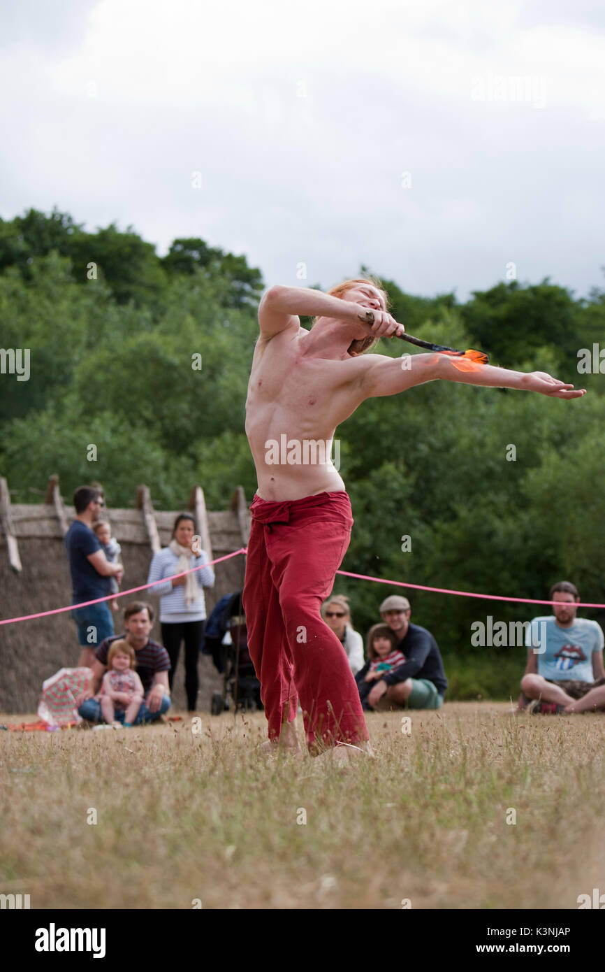 Fire breathing performer Farren 'warms up' for his main act at Dragon Fest 2017 by stroking his arm with flame. - Stock Image