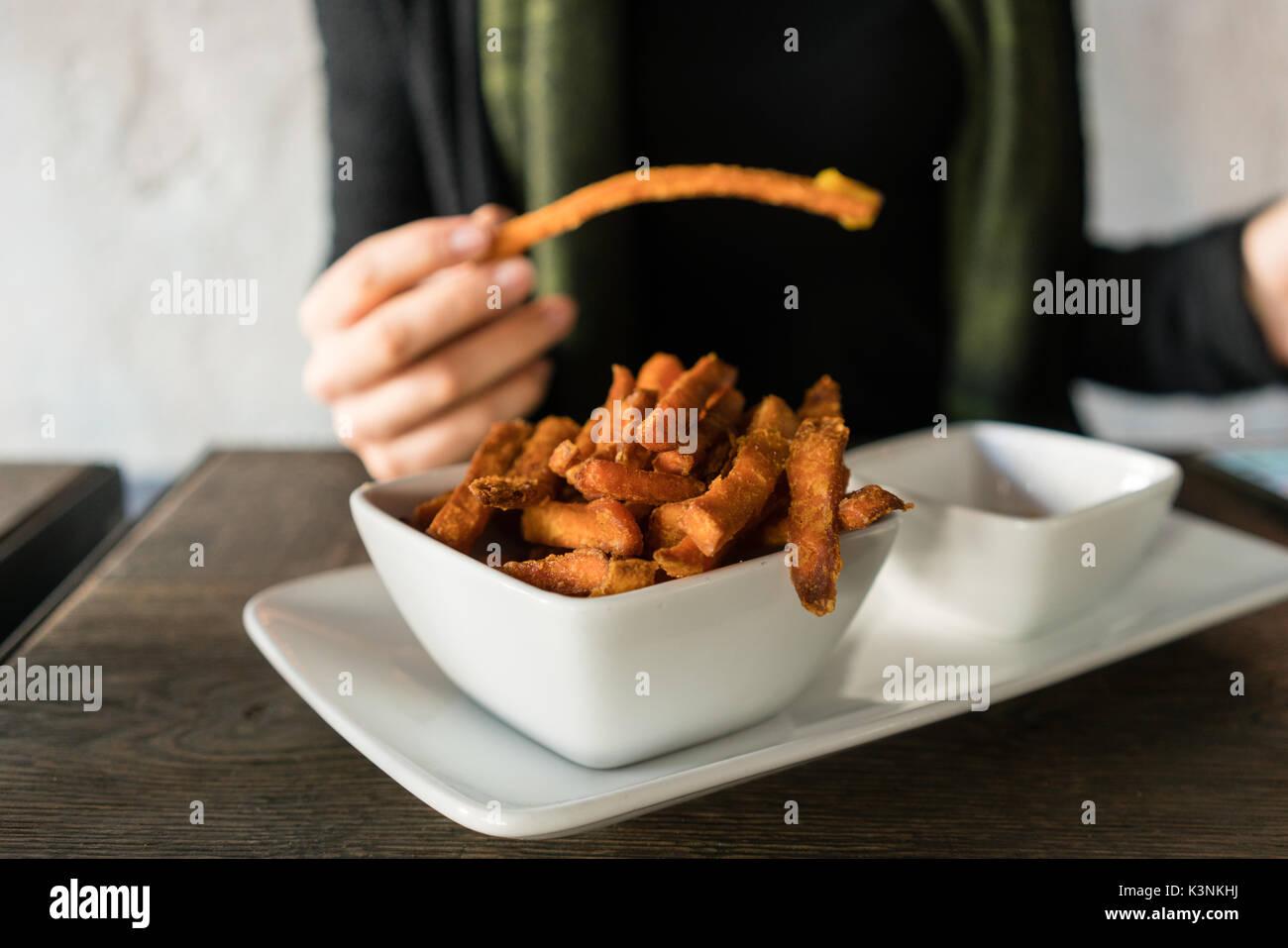 Woman eating sweet potato fries in restaurant - Stock Image