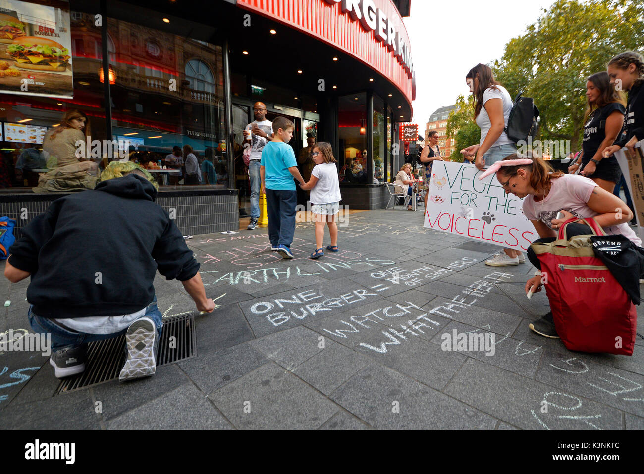 Animal rights protesters outside Burger King Leicester Square attempting to convert the public to become vegan in London. Space for copy - Stock Image