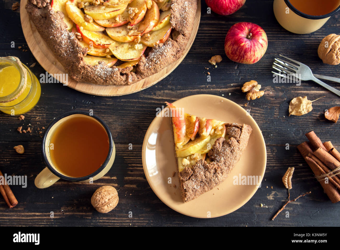 Autumn breakfast with tea and apple pie. Homemade seasonal organic food - apple galette with honey, walnuts and cinnamon for Thanksgiving day. - Stock Image