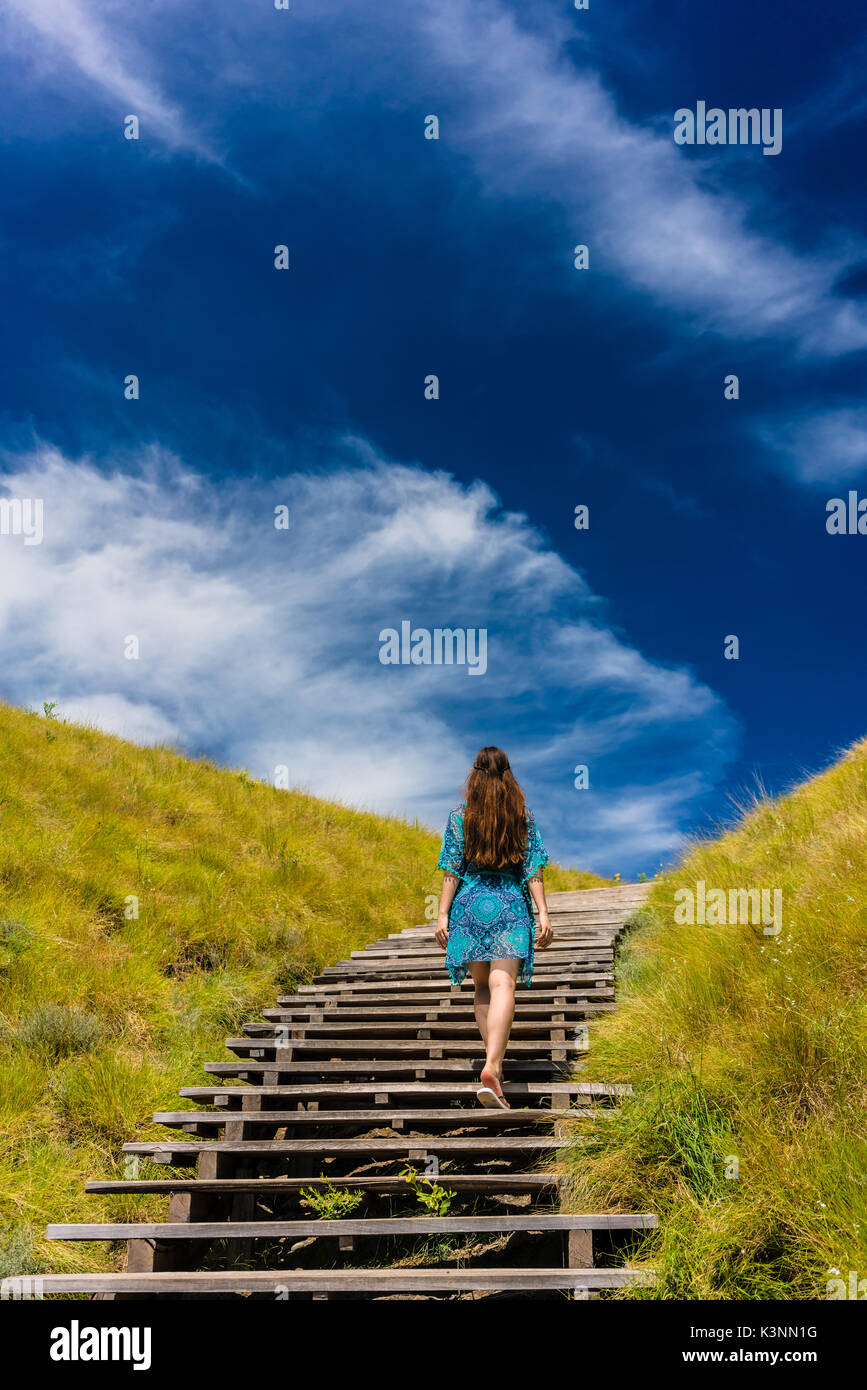 Young woman climbing stairs outdoors in an idyllic travel destin Stock Photo