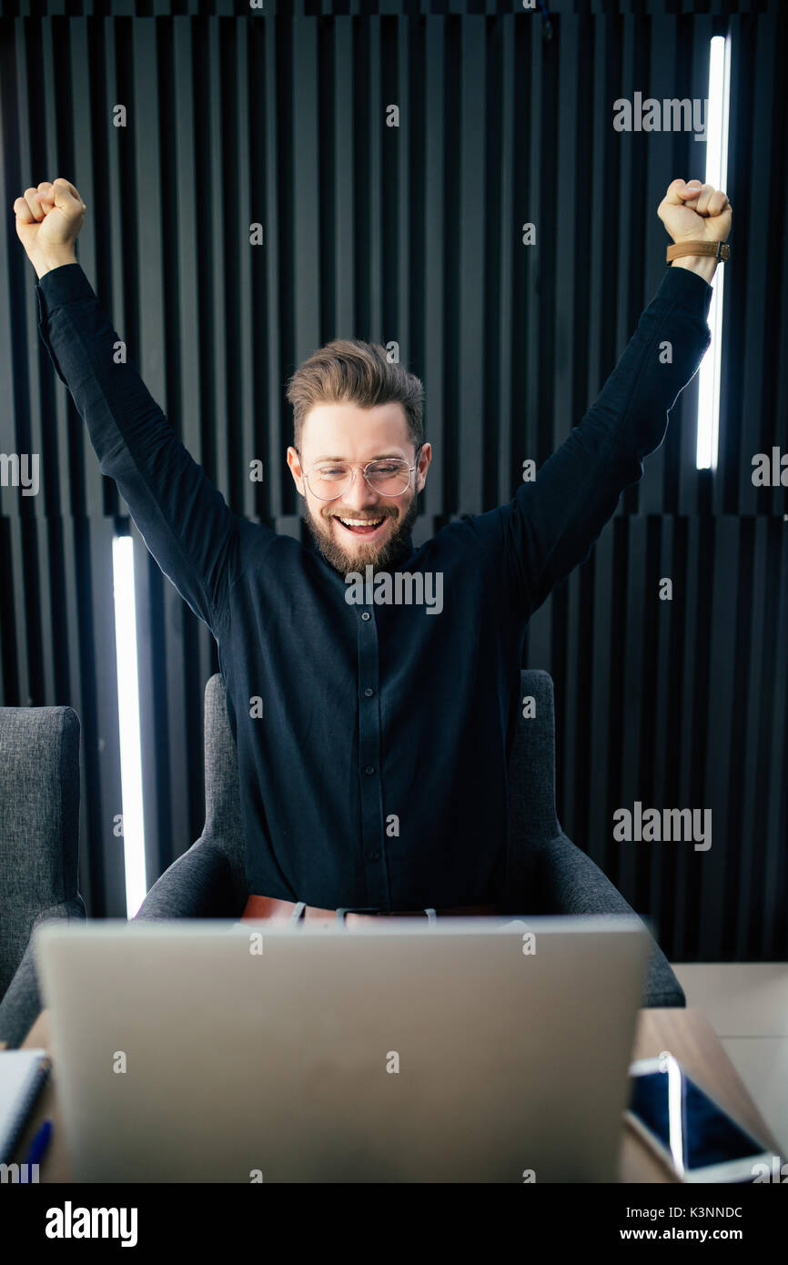 Happy businessman in suit raising hands looking at laptop, celebrating victory, stock trading win, got job interview invitation. - Stock Image