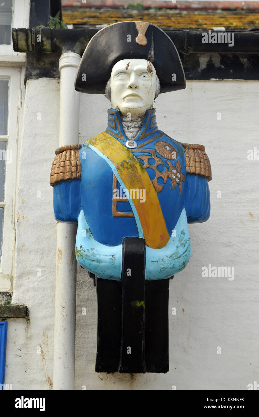 A ships figurehead on the wall outside of a building or property as decoration or adornment features dressed in gheaorgian naval officers uniform - Stock Image