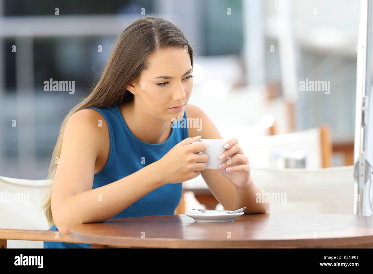 single longing pensive woman sitting in a coffee shop - Stock Image