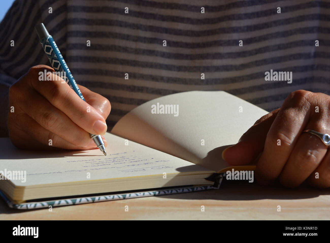 phD student writing list of aims in a notebook / journal - Stock Image