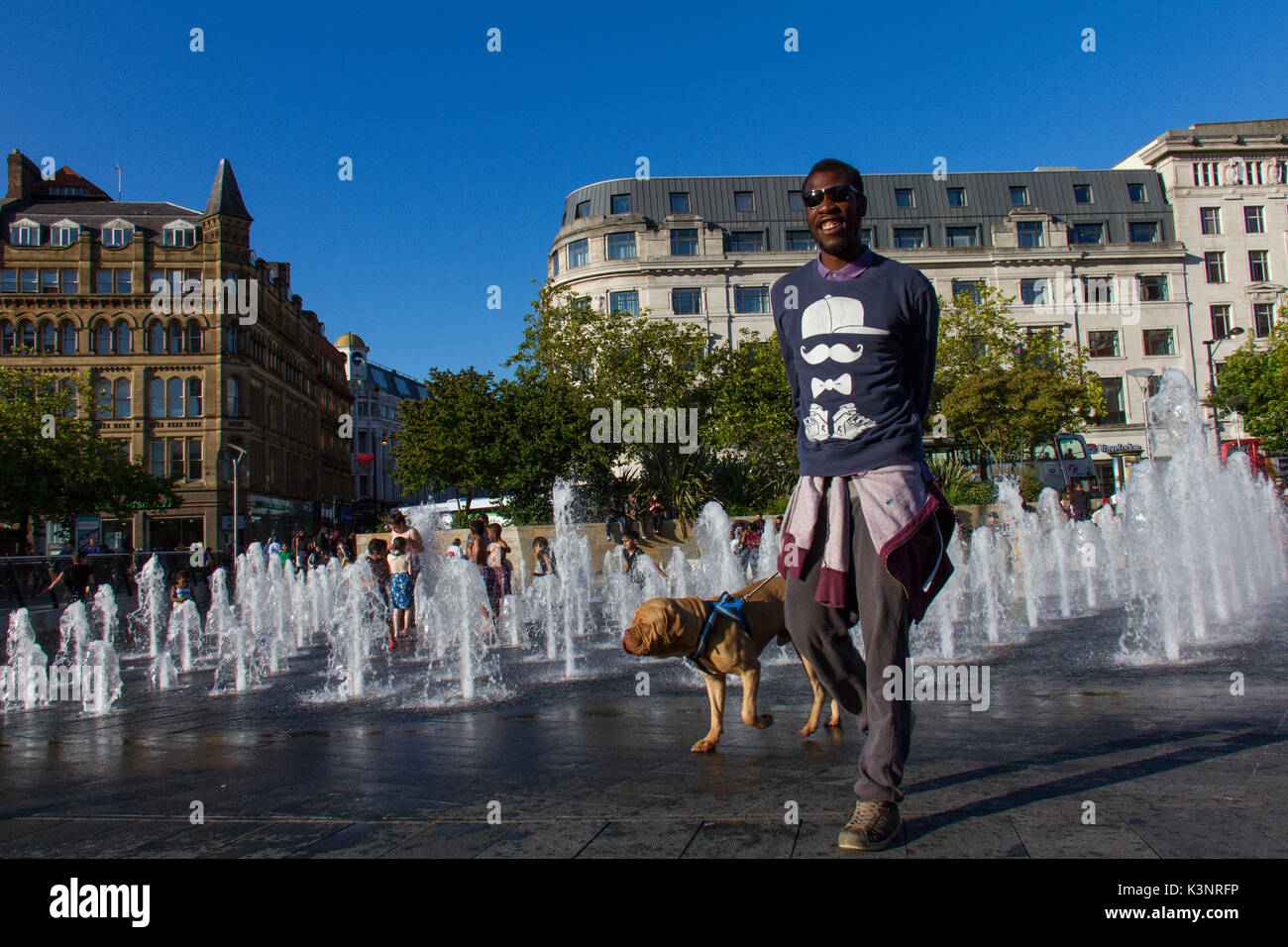 Manchester, United Kingdom - 15 August, 2017: Man and his dog walk by the Picadilly Gardens water fountains in Manchester city centre on a sunny day - Stock Image
