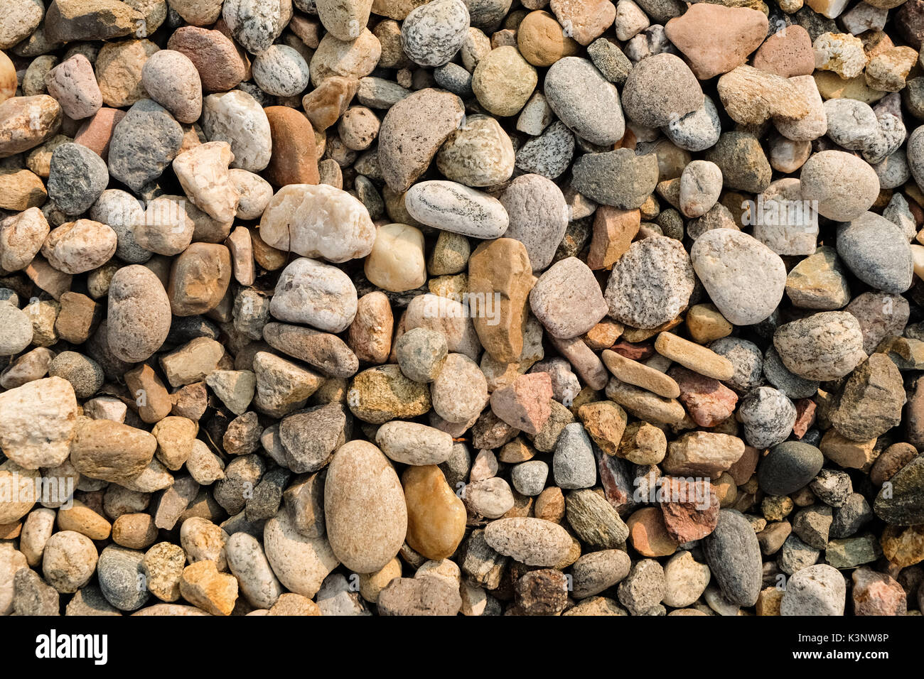 Close up of rounded and polished beach rocks background - Stock Image