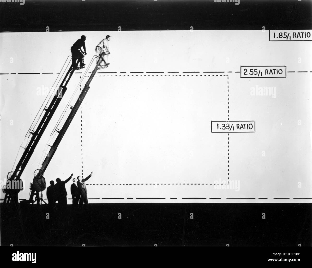 Y FRANK FREEMAN, Vice President of Paramount Pictures, shows ADOLPH ZUKOR, Paramount Board Chairman, the high and wide screen which is capable of showing VistaVision. the dotted line shows how the ordinary motion picture screen size compared with the big VistaVision screen. The broken line shows the comparison of 2.55/1 ration screen with high 1.85/1 ration VistaVision screen - Stock Image