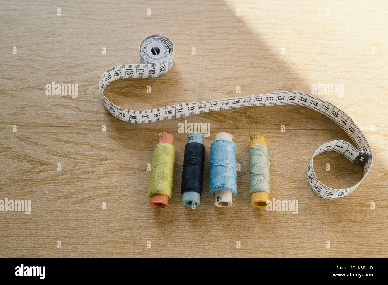 Sewing still life - different color cotton thread spools, thimble, needle, measuring tape - Stock Image