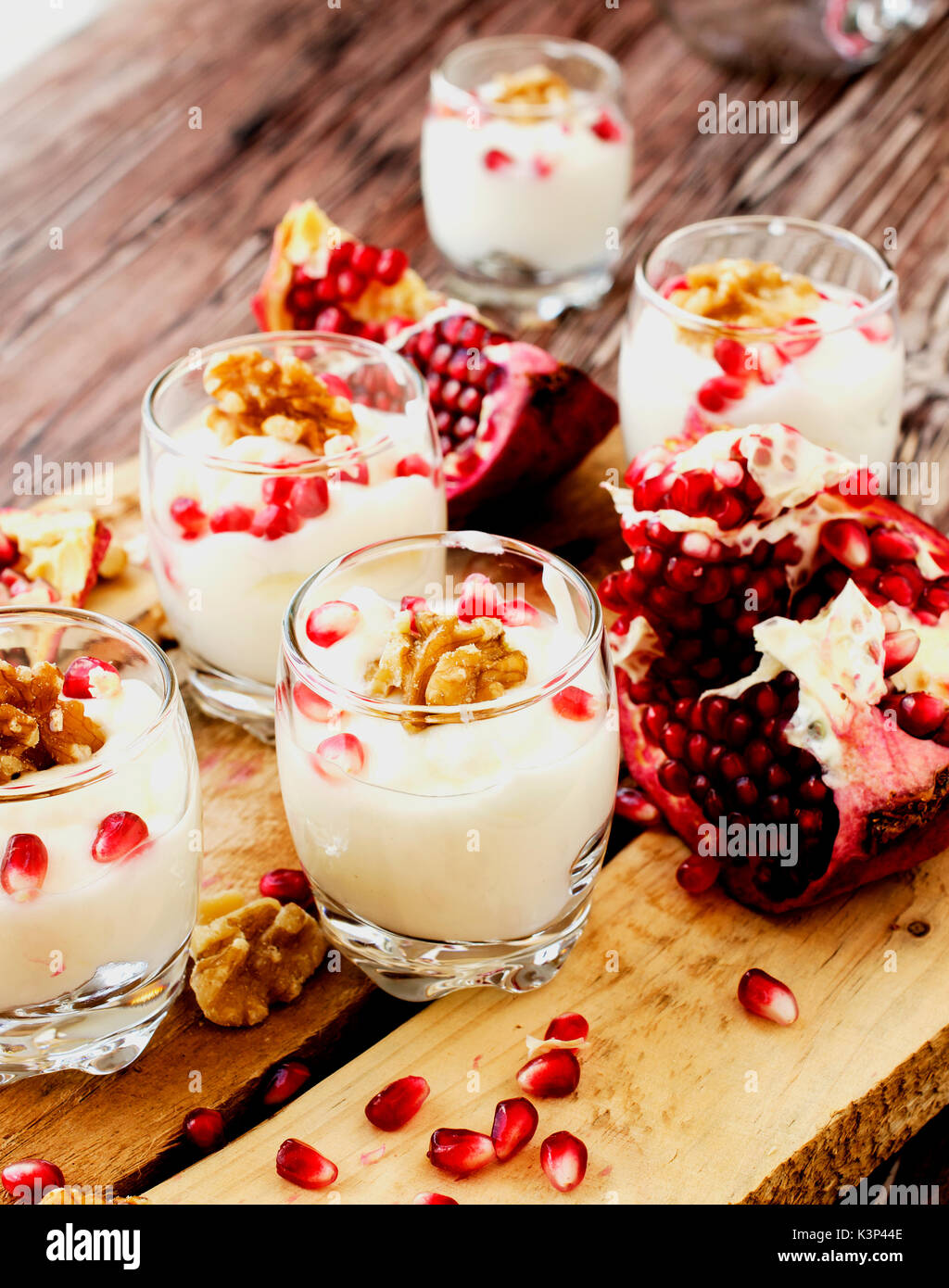 yogurt dessert with walnuts and fresh pomegranate on the wooden table, selective focus - Stock Image