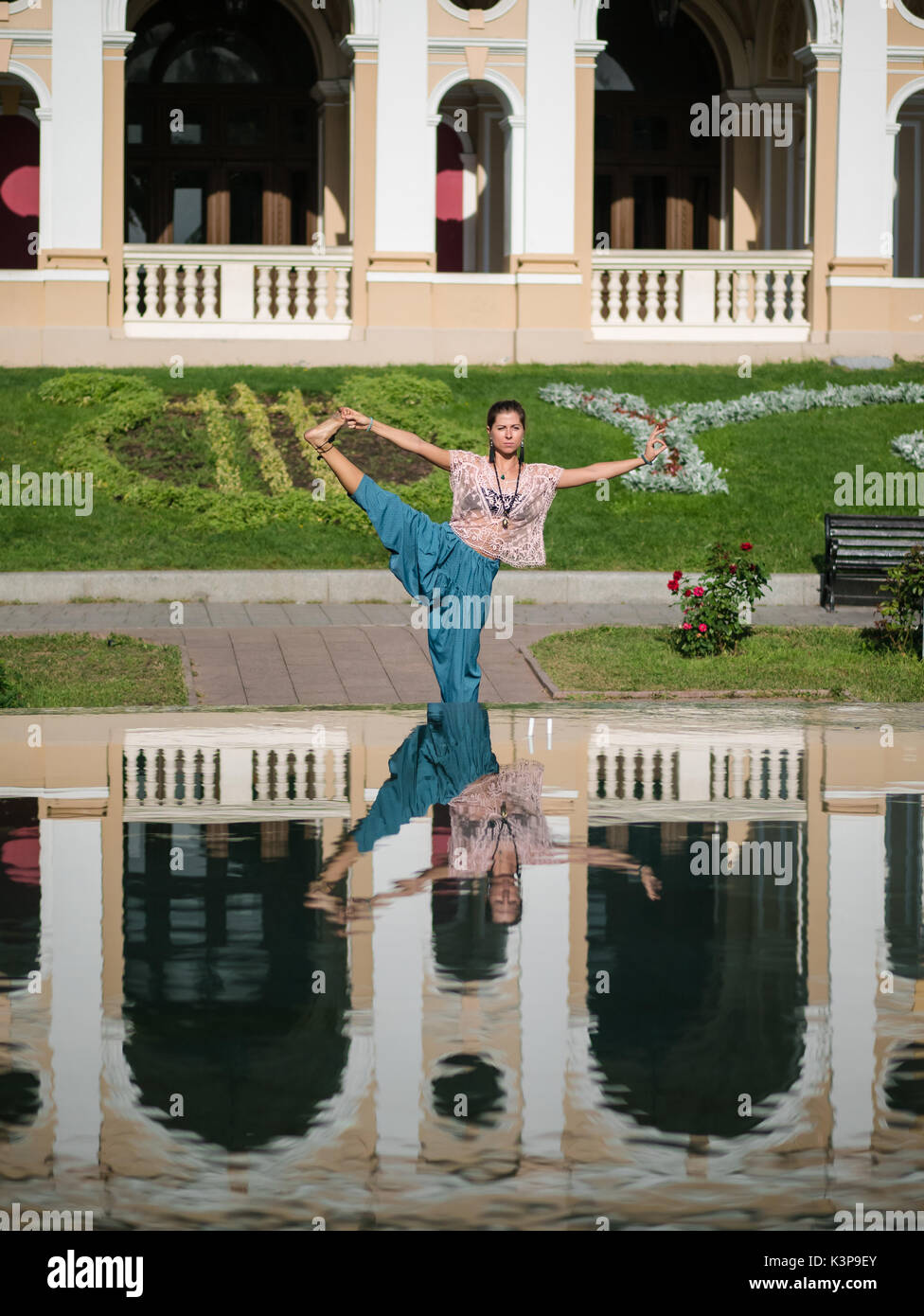 Reflection in the water of a sportive woman making stretching bent during workout in the city. Girl practicing yoga near fountain, beautiful architect - Stock Image