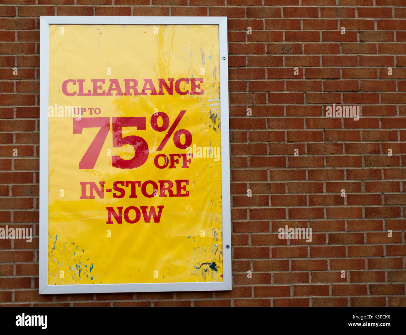 75 percent off in store now retail store clearance sale sign mounted on brick wall - Stock Image