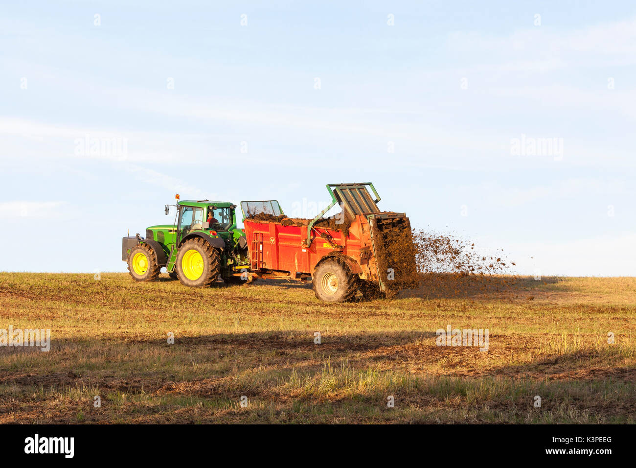 Farmer fertilizing a fallow agricultural field with natural manure using a muck spreader in  golden evening light on the skyline., Dung is spraying ou - Stock Image