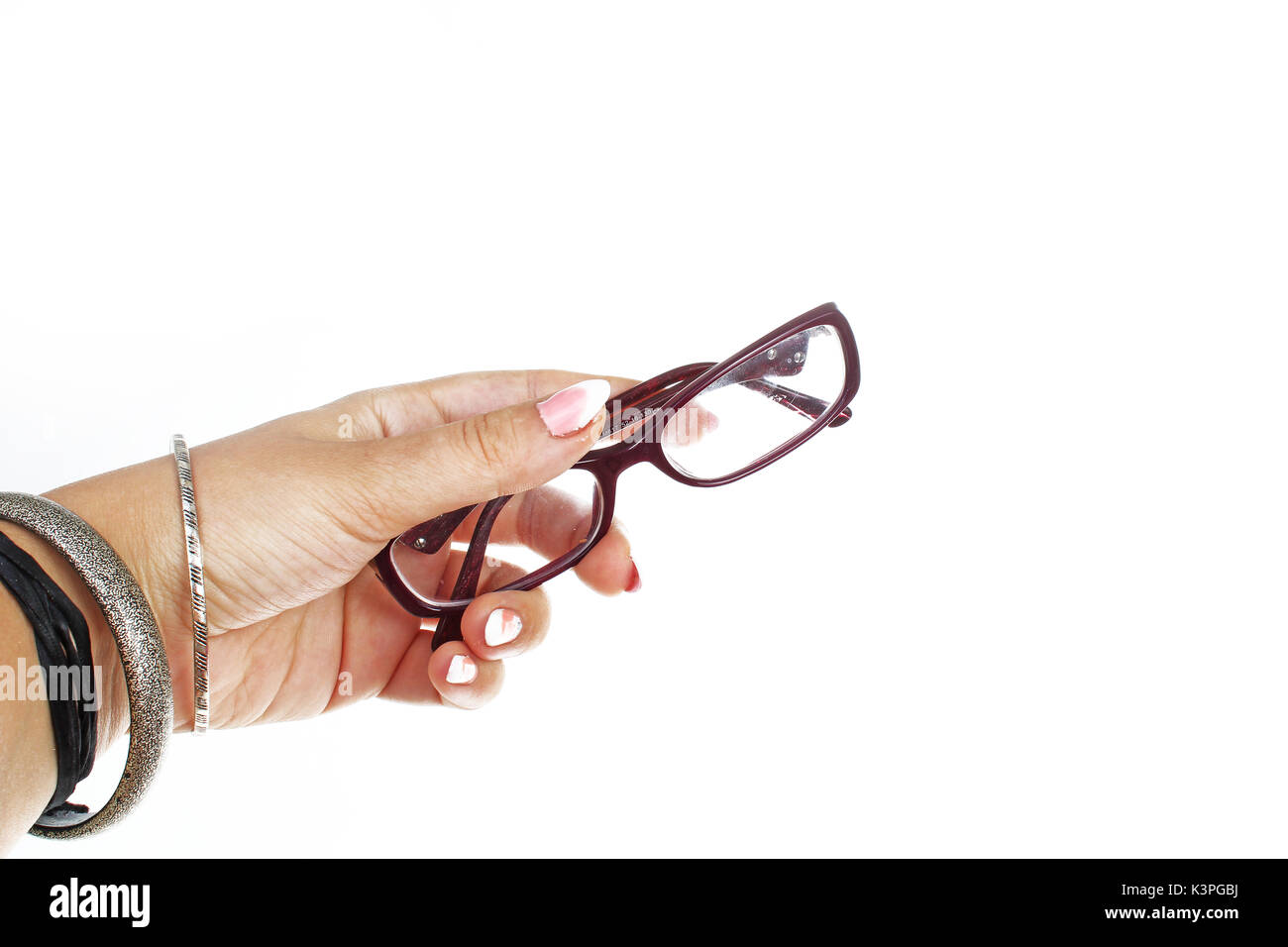 Woman hand holding spectacles eyewear eye glasses on isolated white cutout background. Studio photo with studio lighting easy to use for every concept - Stock Image