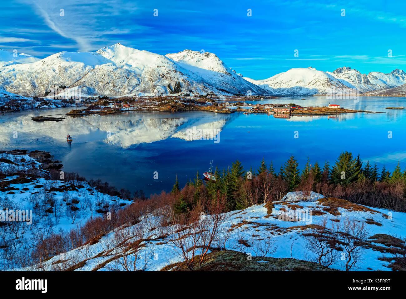 Snow coated Mountains reflect on the Waters of Austnesfjorden, Sildpollen, Lofoten Islands, Norway - Stock Image