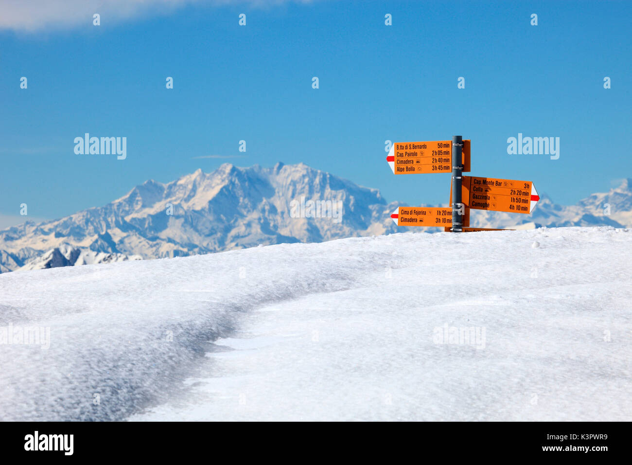 An indications sign almost covered by snow with Monte Rosa in the background seen from passo di San Lucio, Val Cavargna, Province of Como, Lombardy, Italy - Stock Image