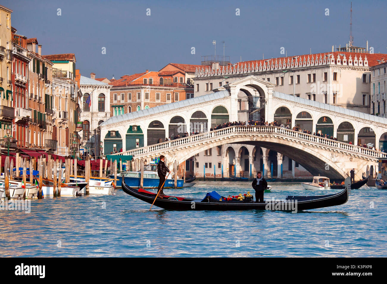 A gondola crossing the Grand Canal right in front of the Rialto Bridge, one of the most recognizable Venetian landmarks  Venice, Veneto Italy Europe - Stock Image