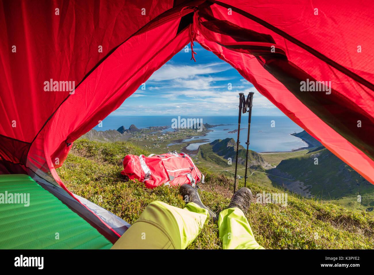 Tent and hiker on mountain top overlooking the sea Sorland Vaeroy Island Nordland county Lofoten archipelago Norway Europe - Stock Image