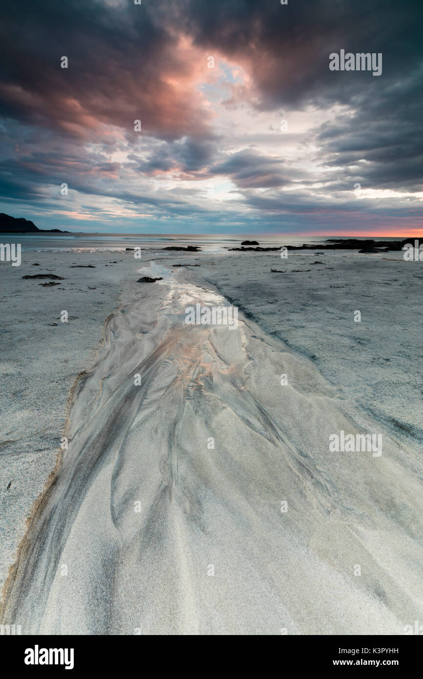 Midnight sun and clouds frame the sandy beach of Skagsanden Flakstad Nordland county Lofoten Islands Norway Europe - Stock Image
