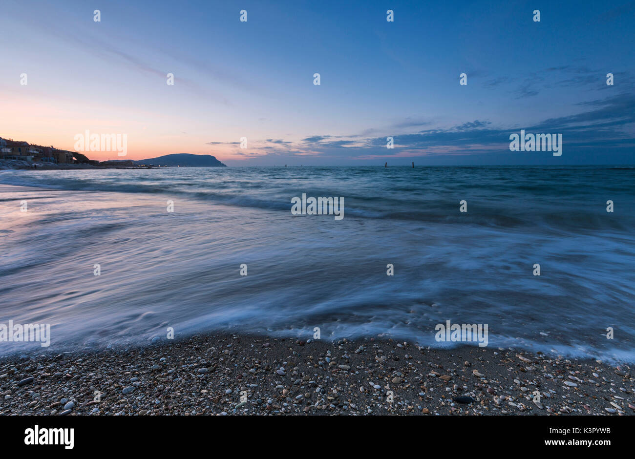 Waves crashing on the beach framed by the blue dusk Porto Recanati