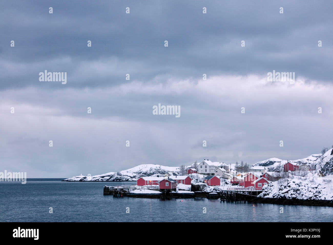 Cold sea and snowy peaks frame the fishing village at dusk Nusfjord Nordland Lofoten Islands Northern Norway Europe - Stock Image