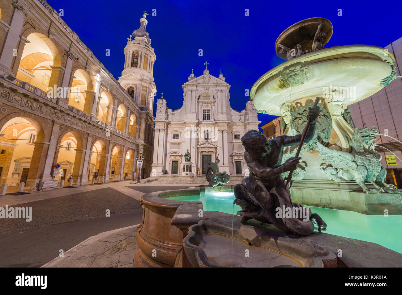 Night view of the Basilica of the Holy House and fountain decorated with statues Loreto Province of Ancona Marche Italy Europe - Stock Image