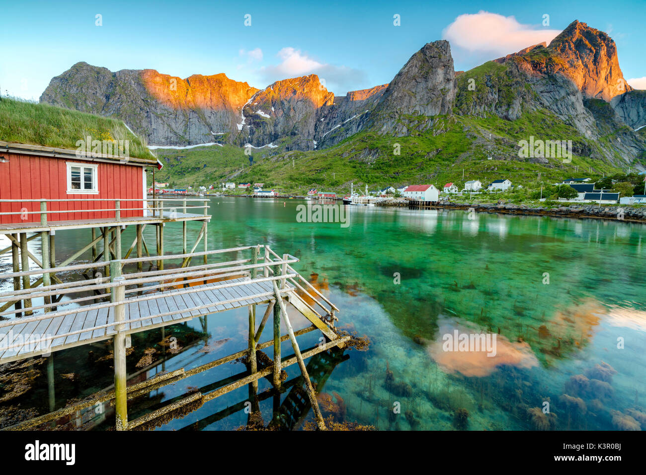 Midnight sun on fishing village and peaks surrounded by clear sea Reine Nordland county Lofoten Islands Northern Norway Europe - Stock Image