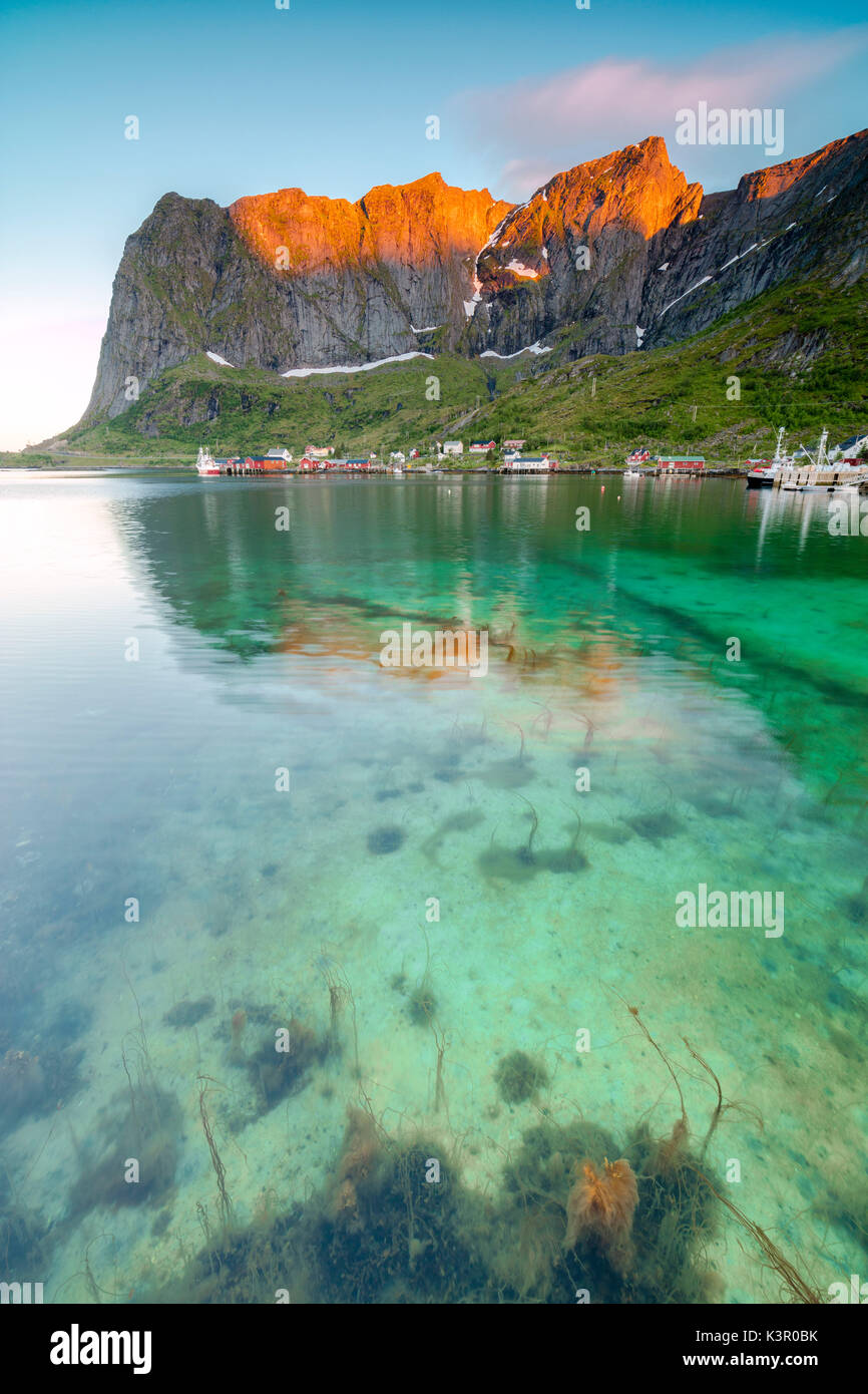 Midnight sun on fishing village surrounded by clear sea and peaks Reine Nordland county Lofoten Islands Northern Norway Europe - Stock Image