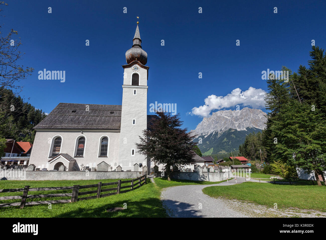 Typical church of alpine village surrounded by peaks and woods Garmisch Partenkirchen Oberbayern region Bavaria Germany Europe - Stock Image