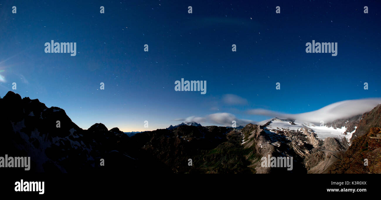 Looking the sky full of stars in a clear night from the refuge Martinelli, the clouds are moving on the glacier of Scerscen and in the distance you can also see Mount Disgrazia, Valmalenco, Lombardy Italy. Europe - Stock Image
