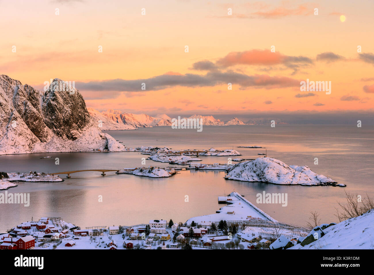 The pink colors of sunset and snowy peaks surround the fishing villages Reine Nordland Lofoten Islands Norway Europe - Stock Image