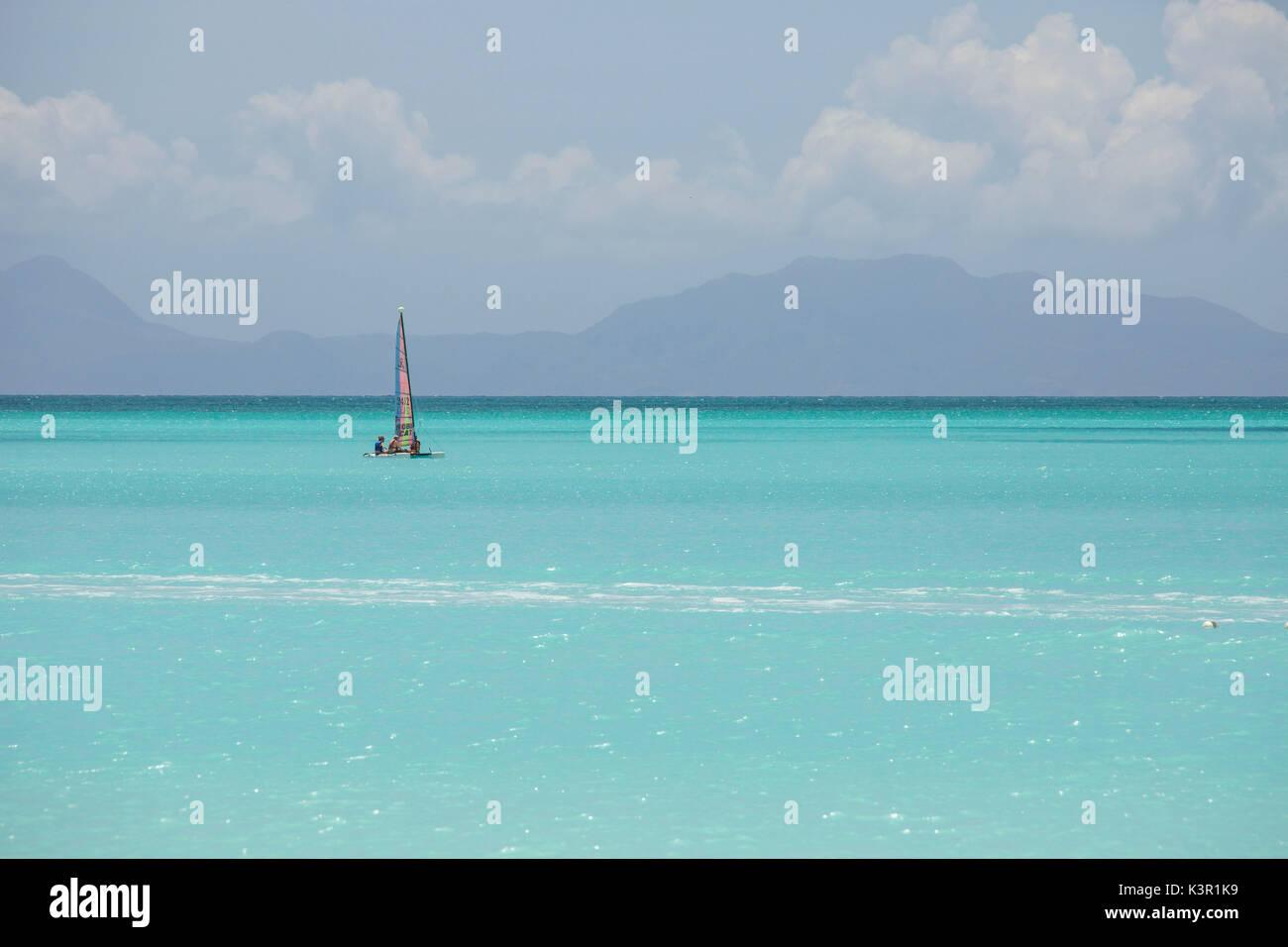A catamaran in the crystalline waters of the Caribbean Sea Jolly Beach Antigua and Barbuda Leeward Island West Indies - Stock Image