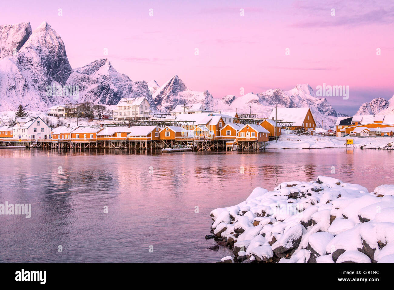 The colors of dawn frames the fishermen houses surrounded by snowy ...