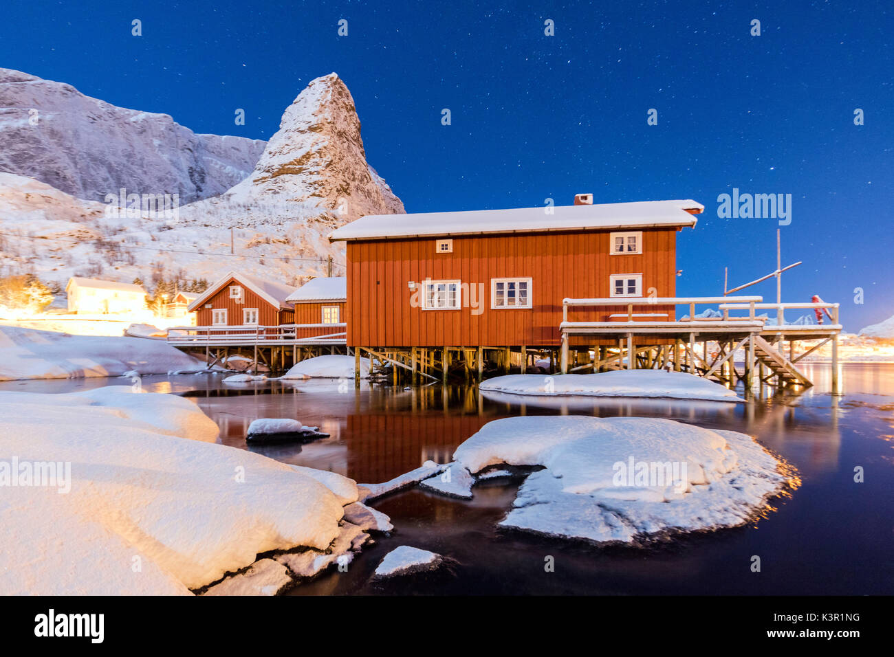 Starry night on the snowy peaks surrounded by the frozen sea and fishermen houses Reinevagen Bay Lofoten Islands Norway Europe - Stock Image