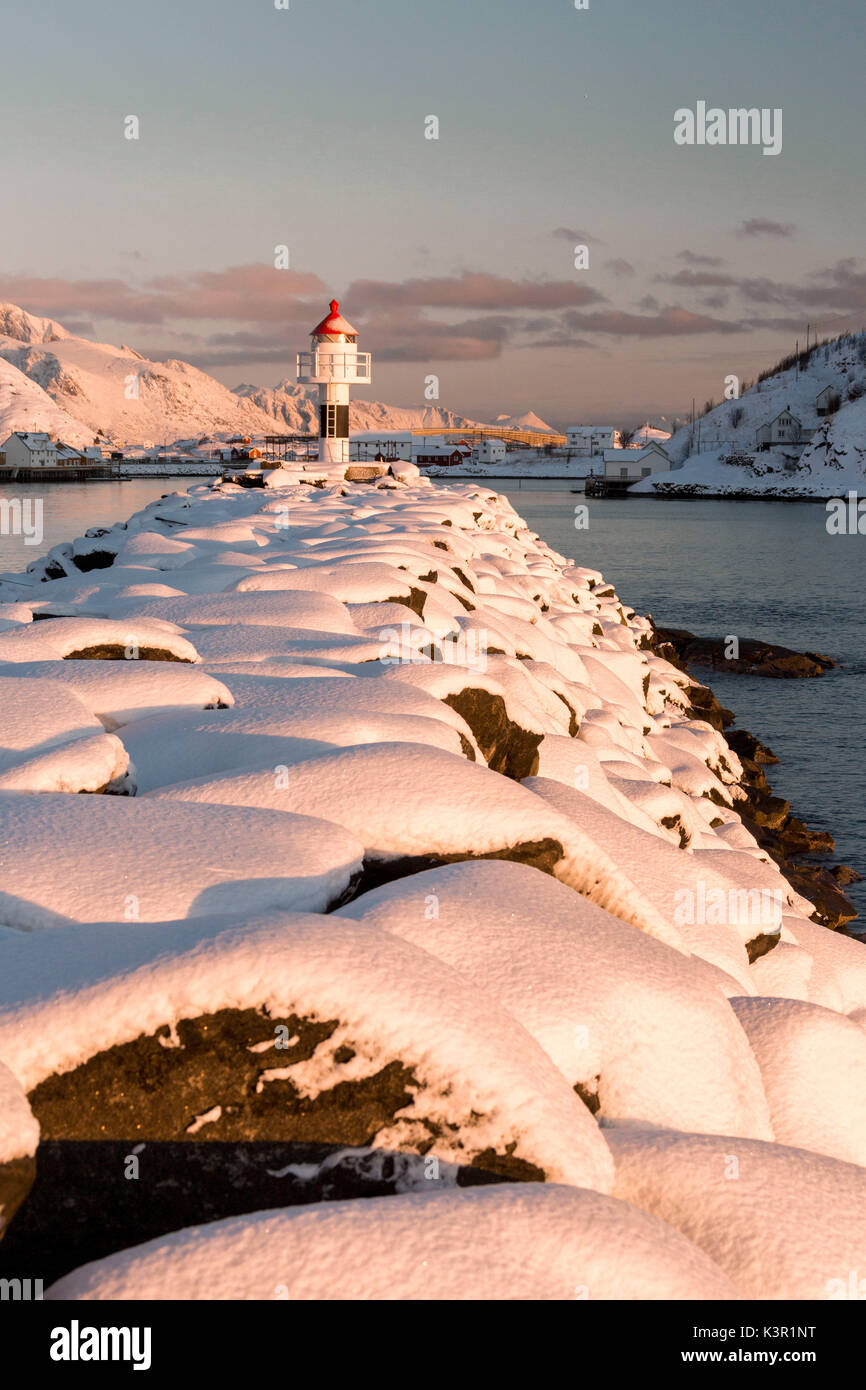 The lighthouse surrounded by snow frames the snowy peaks and the frozen sea Reine Nordland Lofoten Islands Norway Europe - Stock Image