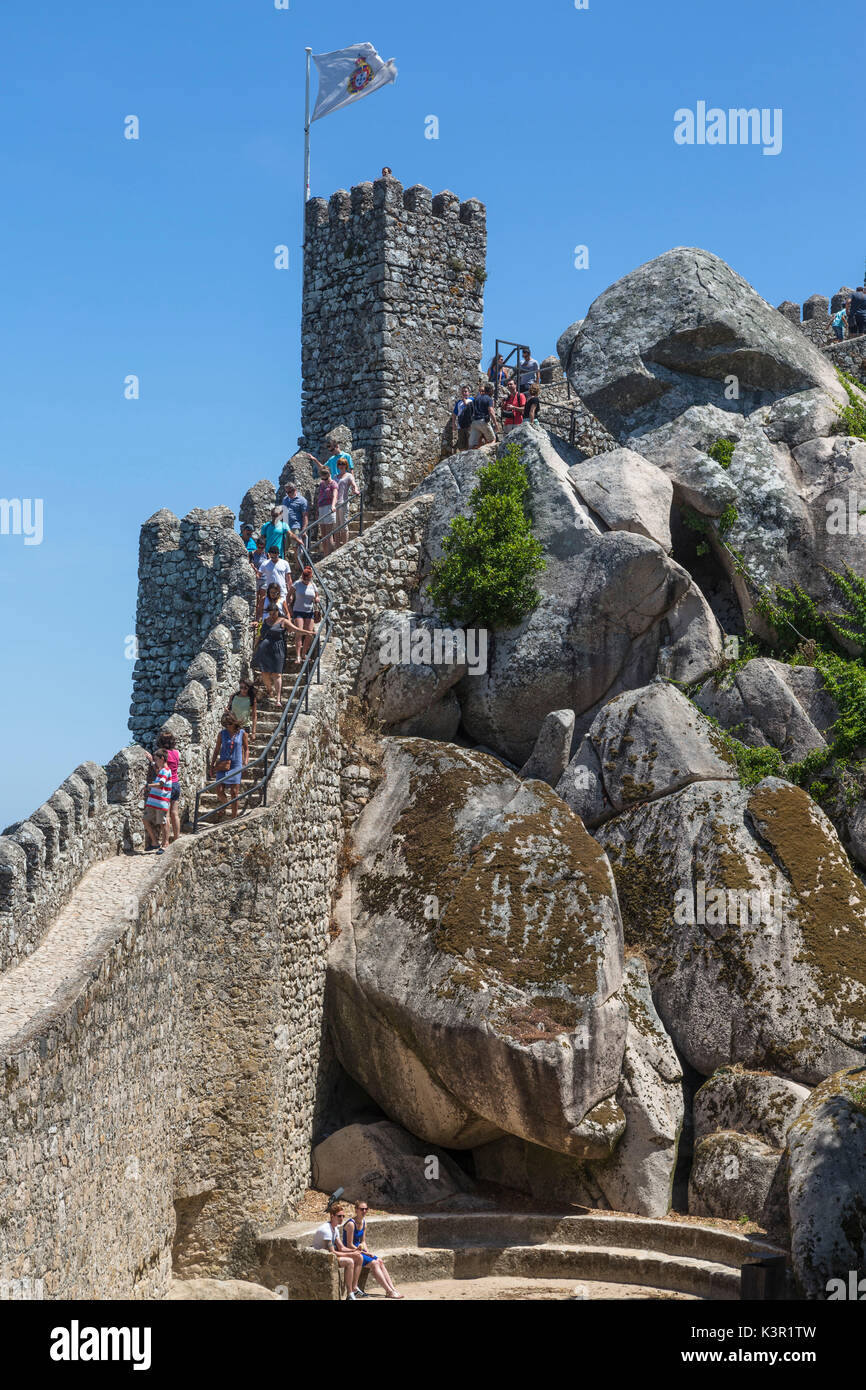 Tourists proceed towards the fortified stone tower of Castelo dos Mouros Sintra municipality Lisbon district Portugal Europe - Stock Image
