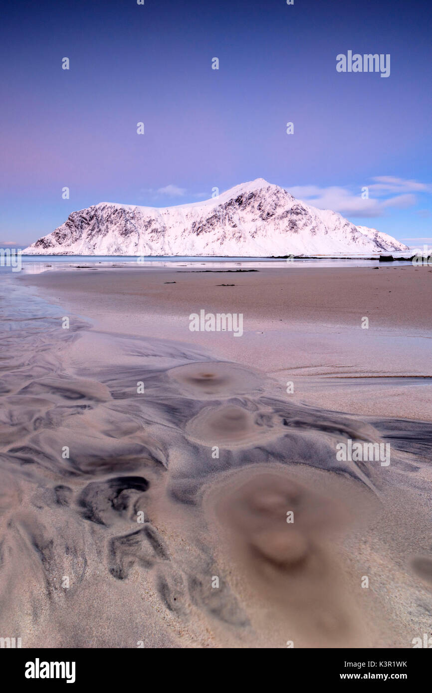 Pink sky and snowy peaks frame the surreal Skagsanden beach at sunset Flakstad Nordland county Lofoten Islands Norway Europe - Stock Image