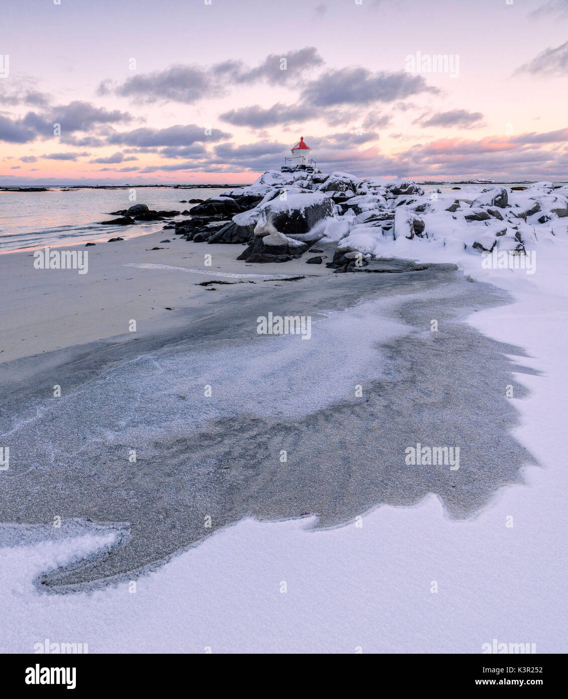 Colorful arctic sunset on the lighthouse surrounded by ice and snow Eggum Vestvagoy Island Lofoten Islands Norway Europe - Stock Image