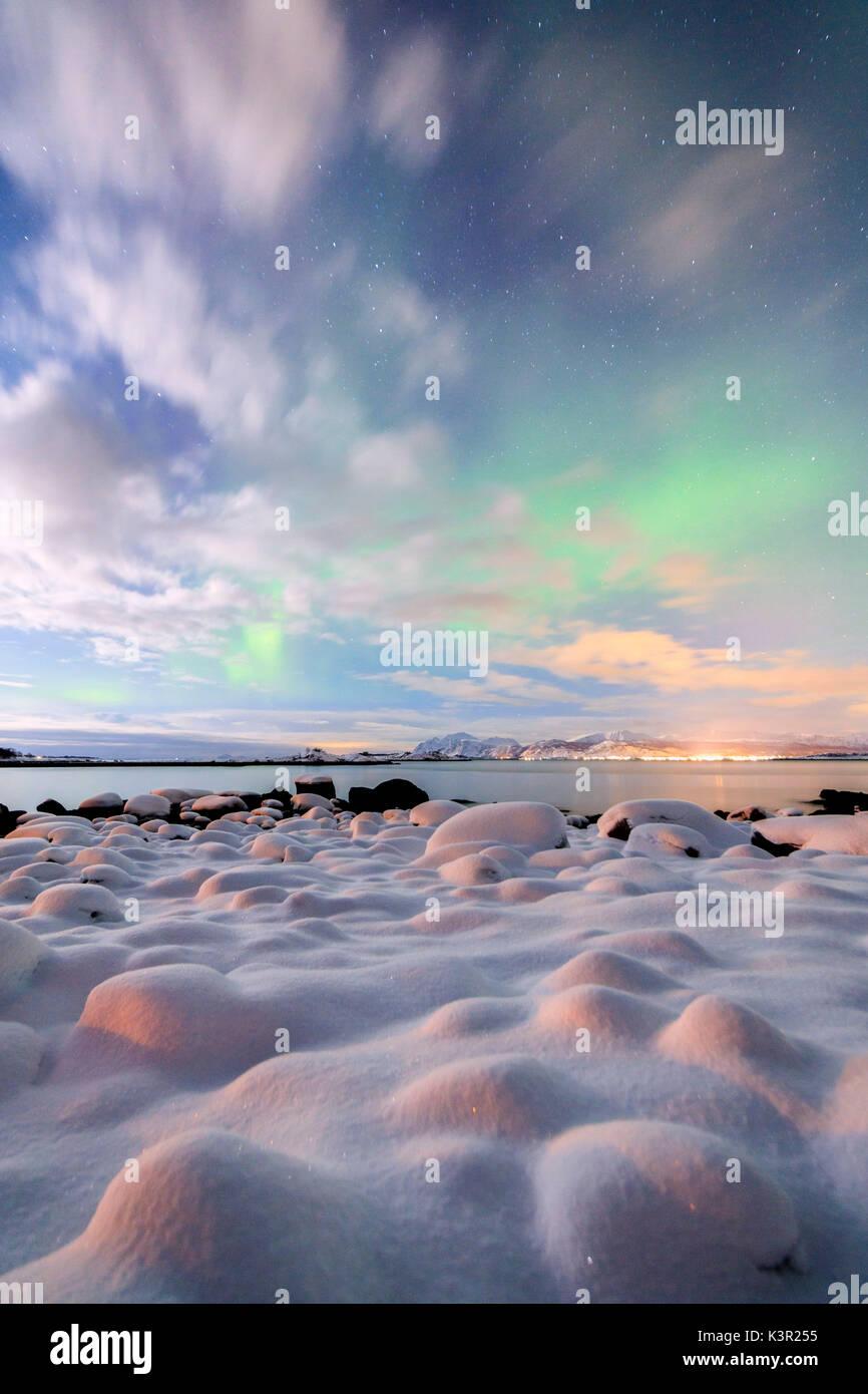 The pink light and the aurora borealis illuminate the snowy landscape on a starry night Strønstad Lofoten Islands Norway Europe - Stock Image