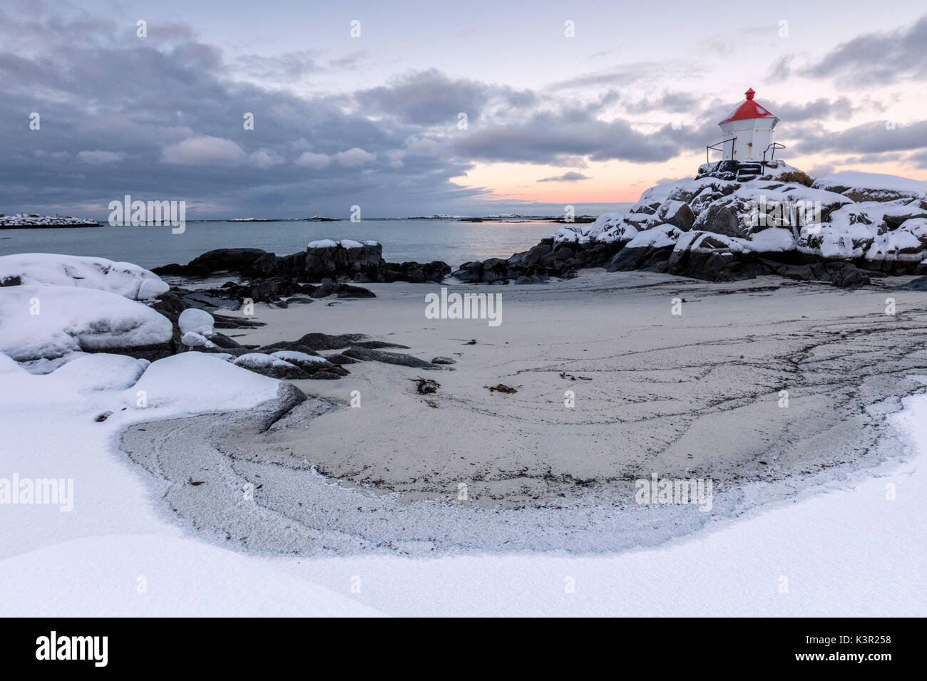 Colorful arctic sunset on the lighthouse surrounded by snow and icy sand Eggum Vestvagoy Island Lofoten Islands Norway Europe - Stock Image