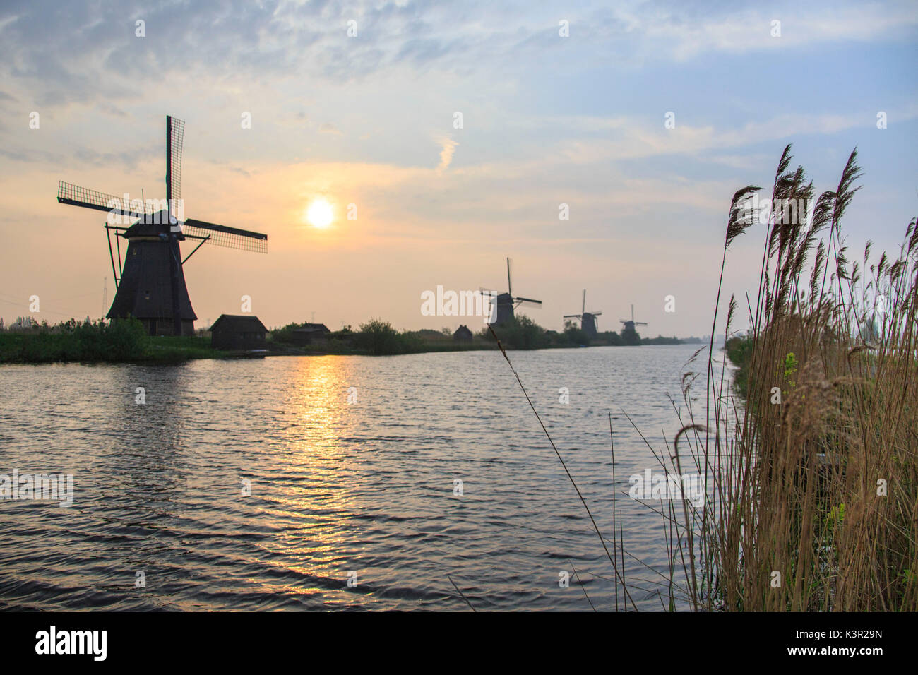 Morning sun just risen shines in the canal where windmills are reflected Kinderdijk Rotterdam South Holland Netherlands Europe - Stock Image