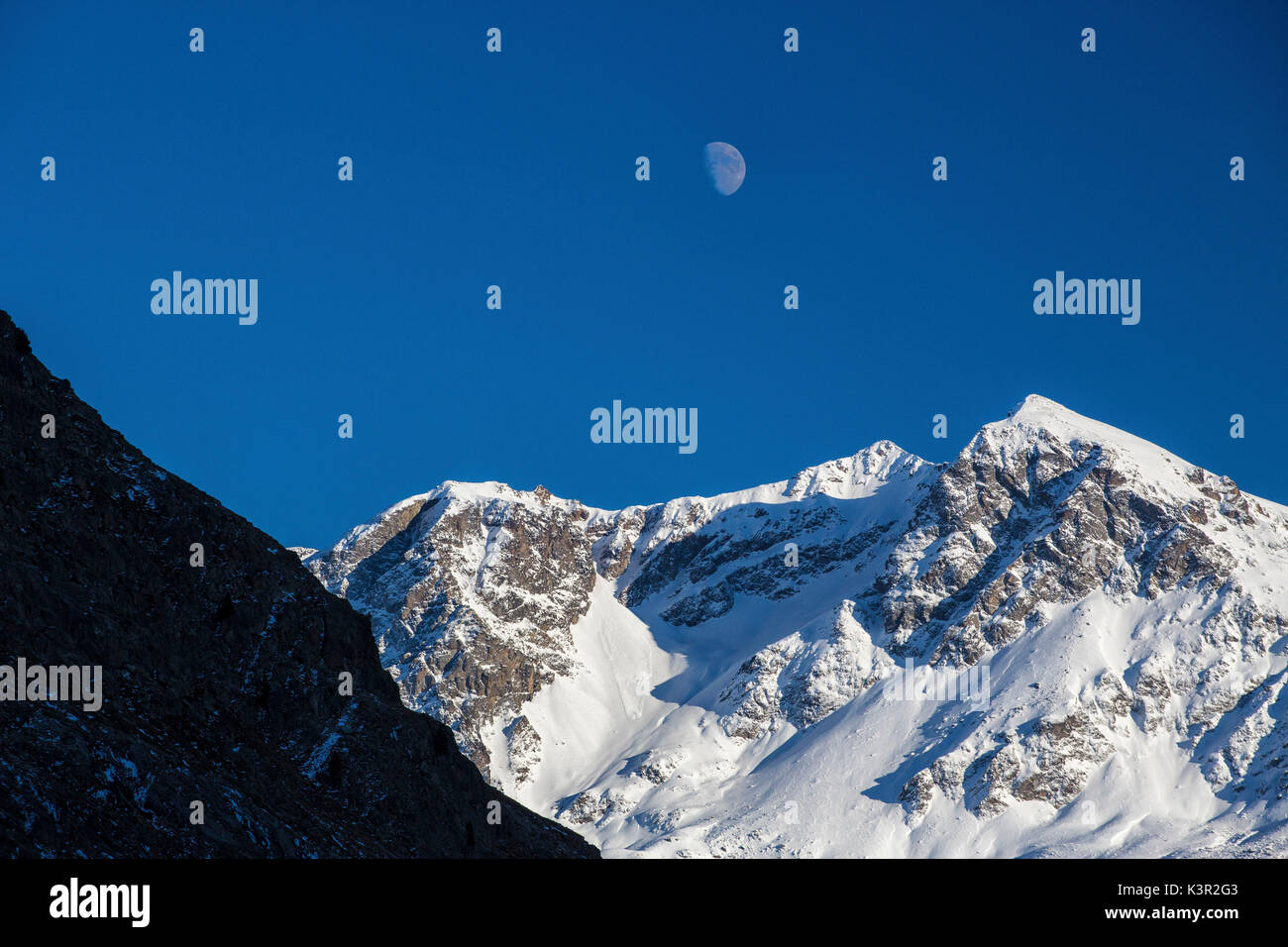 The moon appears above the snowy peaks in the blue sky Julierpass Albula District Canton of Graubünden Switzerland Europe - Stock Image