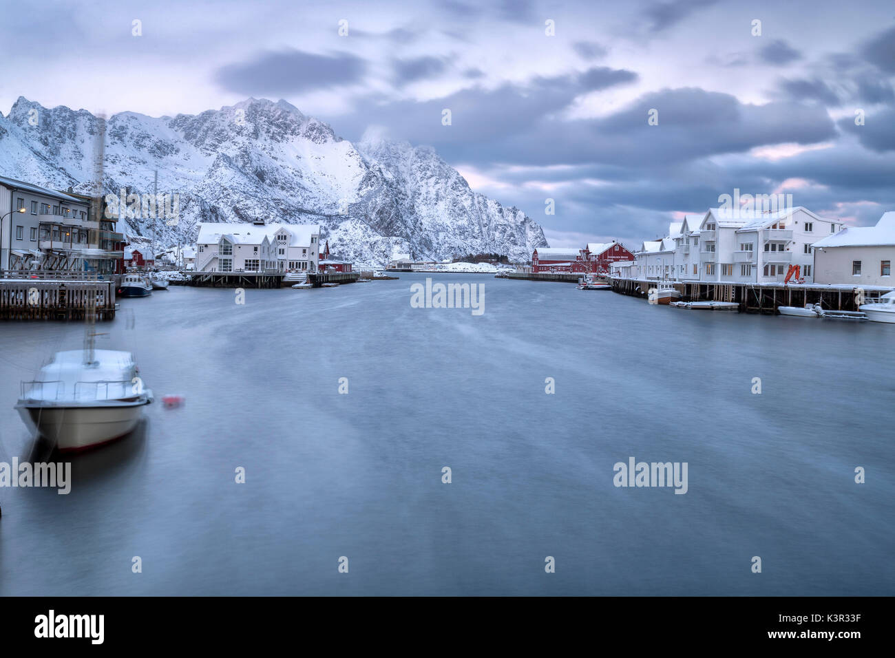 The typical fishing village of Henningsvaer surrounded by snow capped mountains and the cold sea Lofoten Islands Northern Norway Europe - Stock Image