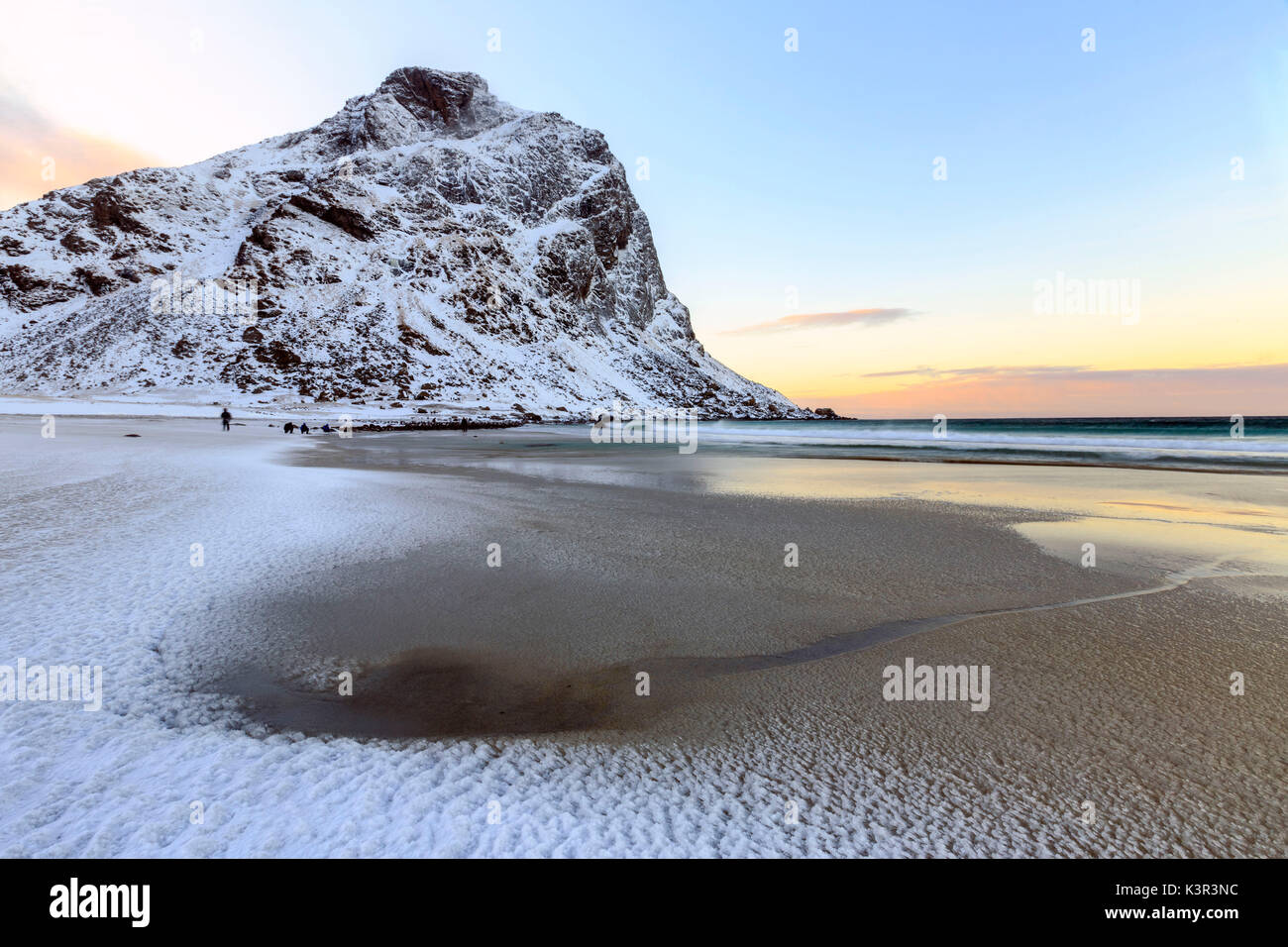 Dawn illuminates the partially snow covered beach of Uttakleiv. Lofoten Islands Norway Europe - Stock Image