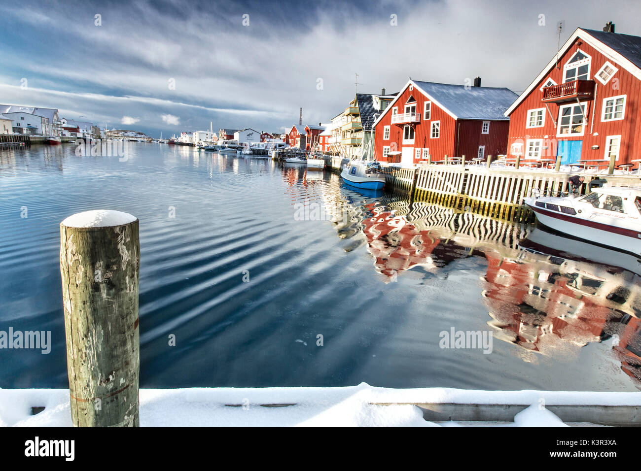 View from the pier on the channel Henningsvaer overlooked by the fishermens houses. Lofoten Islands. Norway. Europe Stock Photo