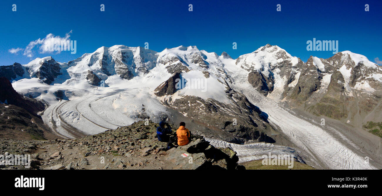 Hikers looking at the vastness of the glaciers of Bernina from Diavolezza Refuge. Engadine, Canton of Graubunden, Switzerland Europe - Stock Image