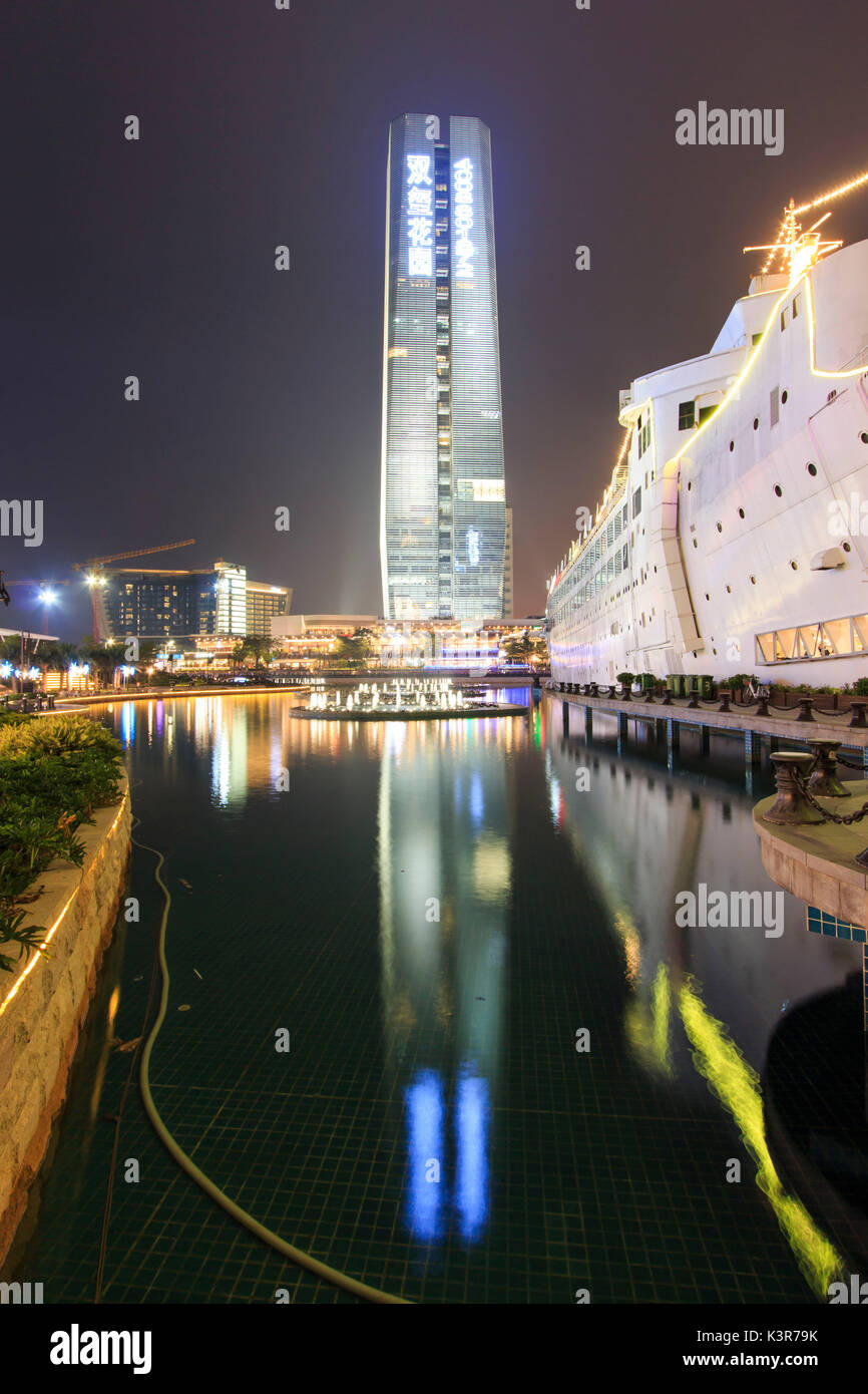 New Sea World Plaza, one of the landmark of Shenzhen, at night with the artificial lake on its center. The ship was originally known as Anceevilla and  was later renamed 'Minghua' by the chinese who bought it, China - Stock Image