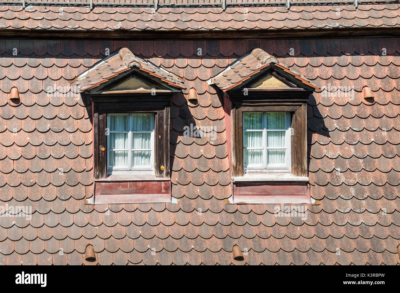 Bamberg, Germany - May 22, 2016: Traditional windows on the tiled roof of old half-timbered colorful house close Stock Photo